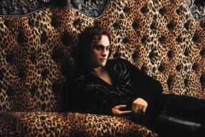 un homme en tenue noire dans un canapé léopard